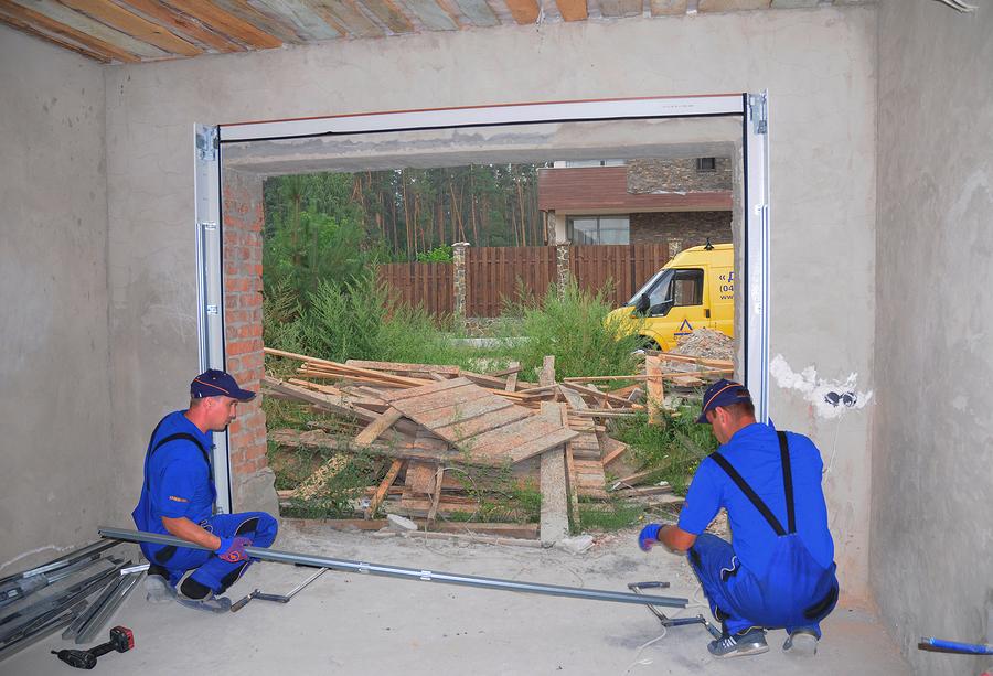 KIEV UKRAINE - January 13 2017: Contractors Installing Garage Door. Step by Step. Installing Garage Door Post Rail and Spring Installation.